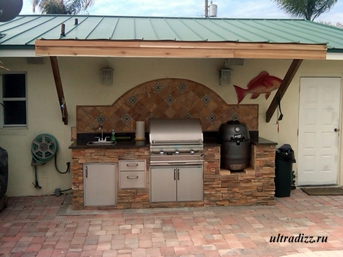 летняя кухня возле стены дома