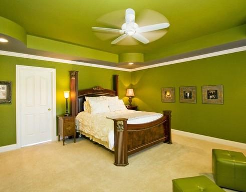 зеленый интерьер спальни с оригинальными кожаными пуфами