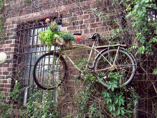 вазон из старого велосипеда на фасаде кирпичного дома