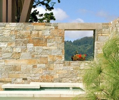 окно в каменном заборе с красивым пейзажным видом