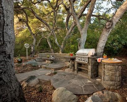 каменная летняя кухня с грилем в саду